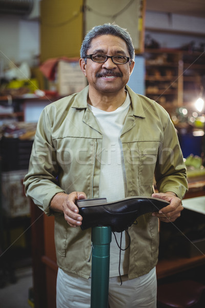 Portrait of smiling shoemaker examining a shoe Stock photo © wavebreak_media
