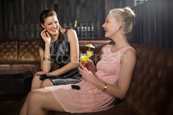 Female friends interacting with each other while having cocktail Stock photo © wavebreak_media
