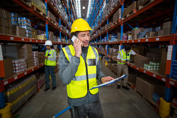 Warehouse worker talking on mobile phone and holding clipboard Stock photo © wavebreak_media