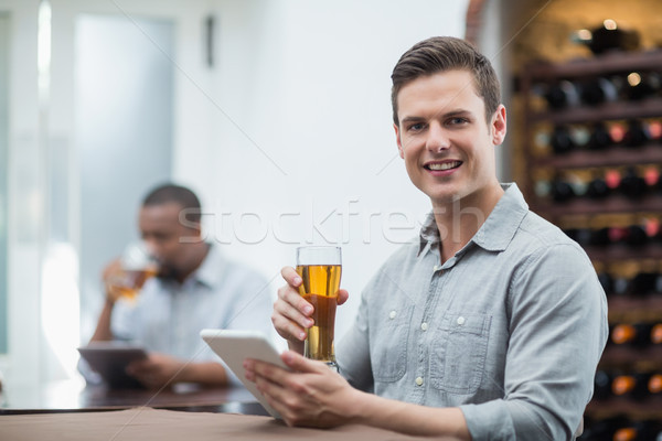 Handsome man holding beer glass while using digital tablet Stock photo © wavebreak_media