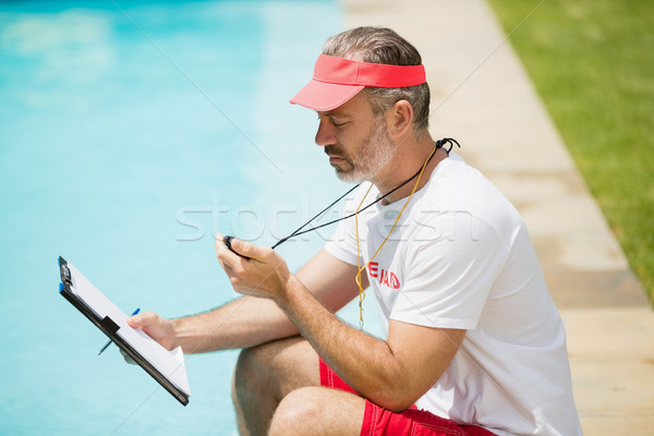 Swim coach looking at stopwatch near poolside Stock photo © wavebreak_media