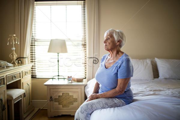 Zmartwiony starszy kobieta posiedzenia bed sypialni Zdjęcia stock © wavebreak_media
