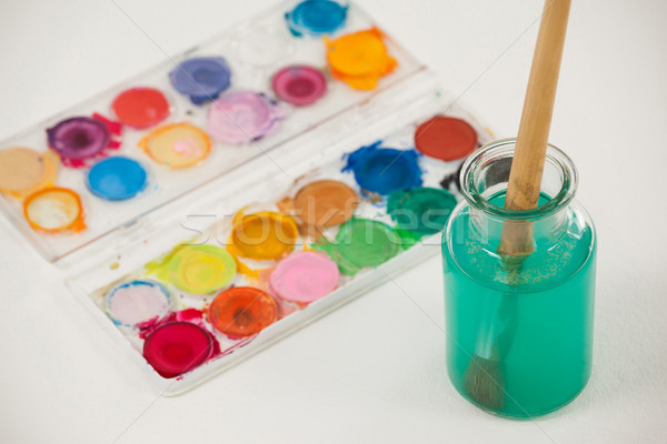 Watercolor palette and paint brush with blue paint dipped into water Stock photo © wavebreak_media