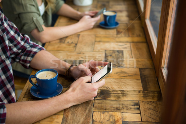 Man and woman using mobile phones in coffee shop Stock photo © wavebreak_media