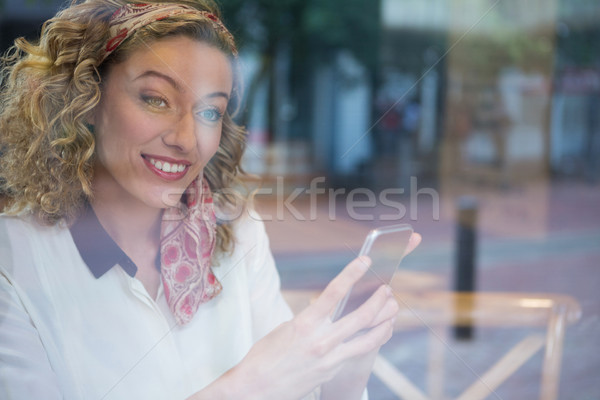Smiling young woman holding smart phone at cafe Stock photo © wavebreak_media