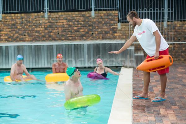 Lifeguard helping swimmers at poolside Stock photo © wavebreak_media