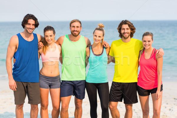 Feliz amigos em pé braço em torno de praia Foto stock © wavebreak_media