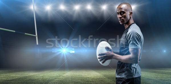 Composite image of portrait of confident athlete standing with rugby ball Stock photo © wavebreak_media