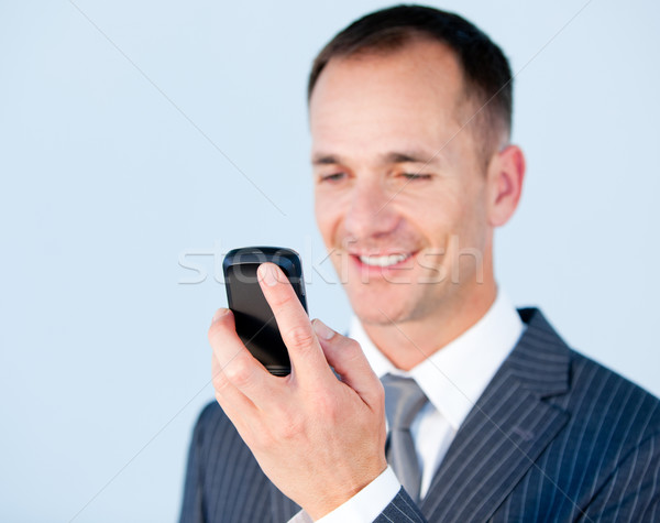 Self-assured businessman sending a text with his  phone Stock photo © wavebreak_media
