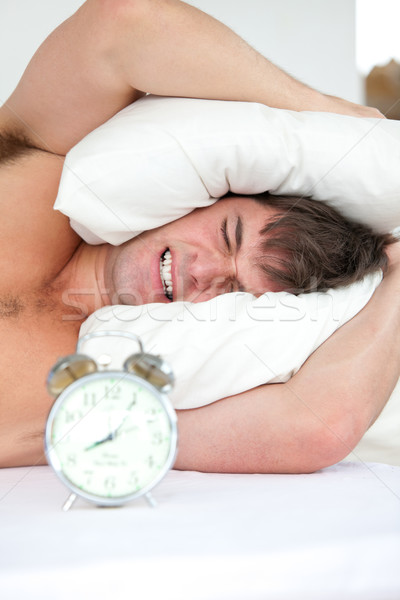 Stressed man woken-up by his alarm clock putting his head under the pillow Stock photo © wavebreak_media