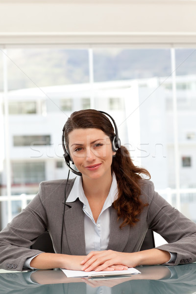Cute businesswoman on the phone with earpiece sitting at a table Stock photo © wavebreak_media
