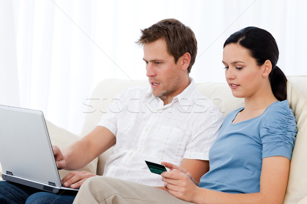 Stock photo: Pretty woman reading code on a credit card for his boyfriend on the sofa at home