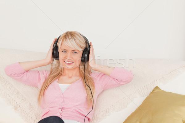 Jól kinéző női zenét hallgat fejhallgató ül kanapé Stock fotó © wavebreak_media