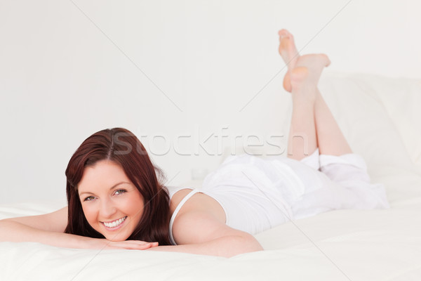 Good looking red-haired female having a rest while lying on her bed Stock photo © wavebreak_media