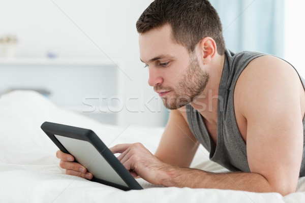 Handsome man using a tablet computer while lying on his belly in his bedroom Stock photo © wavebreak_media