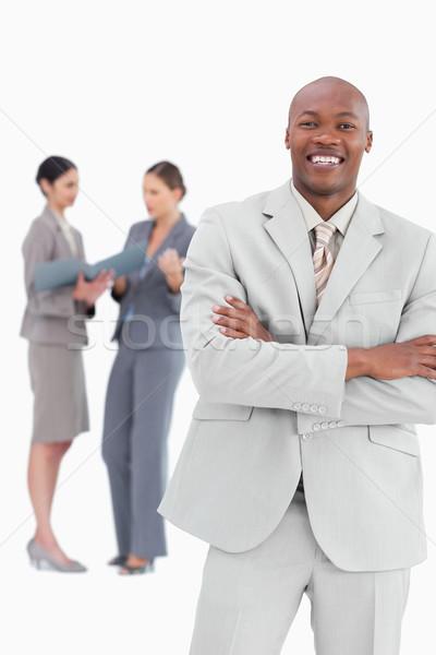Sonriendo empresario los brazos cruzados colegas detrás blanco Foto stock © wavebreak_media