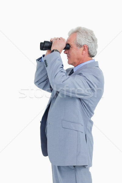 Side view of mature tradesman looking through spy glass against a white background Stock photo © wavebreak_media
