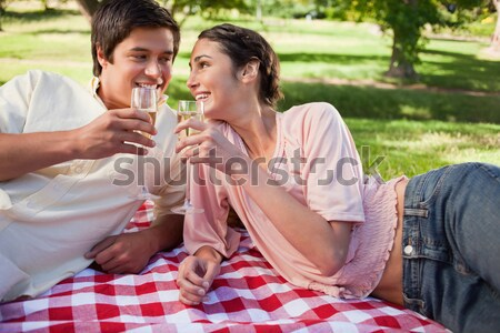 Woman looks ahead while smiling as she is linking arms with her friend and holding glasses of red wi Stock photo © wavebreak_media