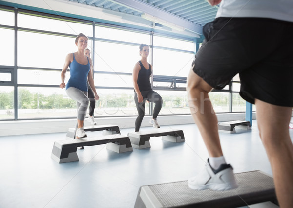 Stock photo: Trainer stepping with aerobic class in gym