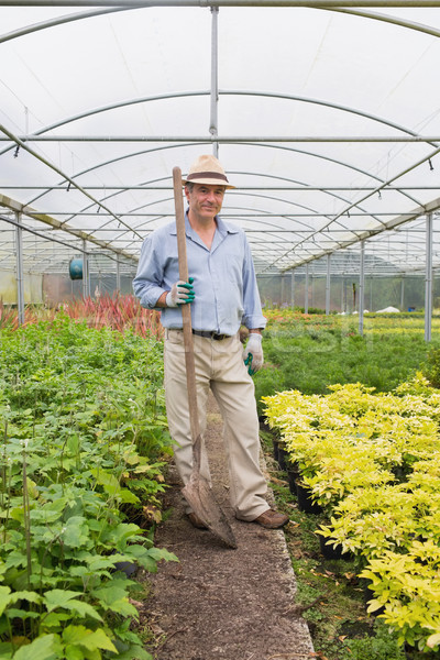 Gardener holding a spade while smiling and standing in greenhouse Stock photo © wavebreak_media