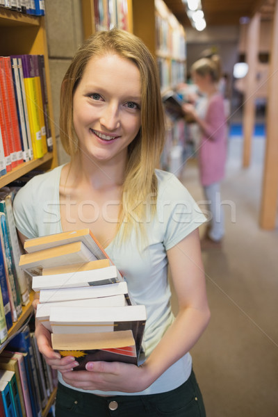 Stock photo: Student standing at a bookshelf at the library while smiling and holding books