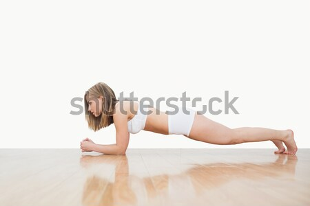 Stock photo: Side view of woman doing push-ups on hardwood floor