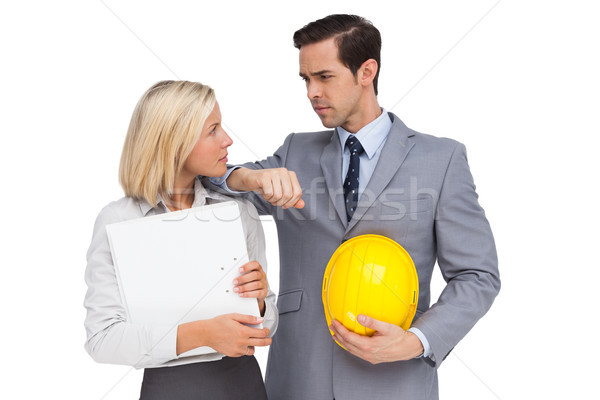 Architects with plans and hard hat looking at each other Stock photo © wavebreak_media