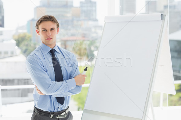 Young stern businessman standing by whiteboard Stock photo © wavebreak_media