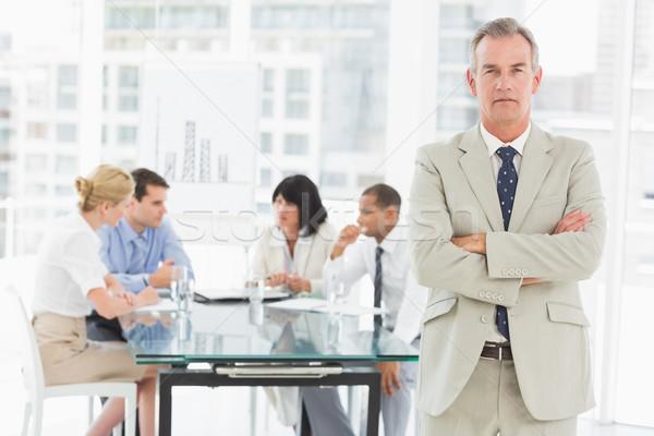 серьезный бизнесмен глядя камеры сотрудников обсуждать Сток-фото © wavebreak_media