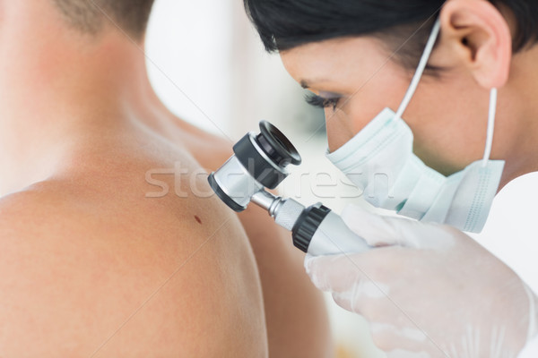 Dermatologist examining mole on patient Stock photo © wavebreak_media