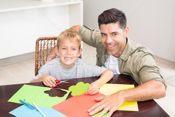 Happy father and son making paper shapes together at the table Stock photo © wavebreak_media
