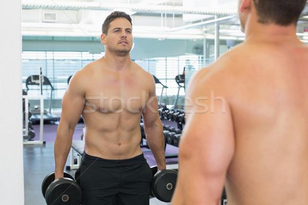 Shirtless bodybuilder lifting heavy black dumbbells looking in m Stock photo © wavebreak_media