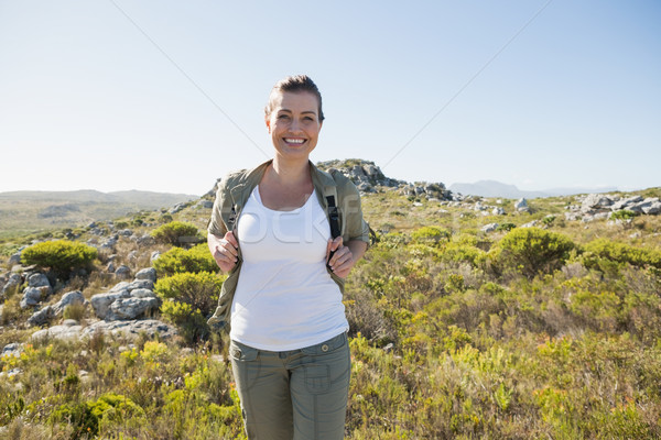Pretty hiker smiling at camera on mountain terrain Stock photo © wavebreak_media