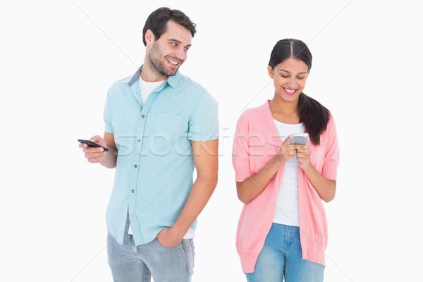 Szczęśliwy para wiadomości tekstowe biały kobiet Zdjęcia stock © wavebreak_media