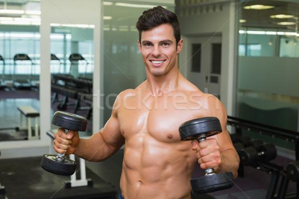 Shirtless muscular man exercising with dumbbells Stock photo © wavebreak_media