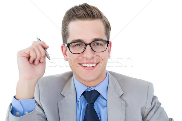 Nerdy businessman holding pen smiling at camera Stock photo © wavebreak_media