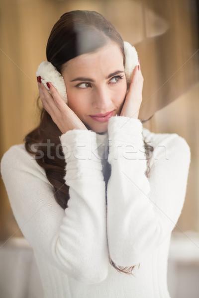 Pretty brunette with ear muffs thinking Stock photo © wavebreak_media