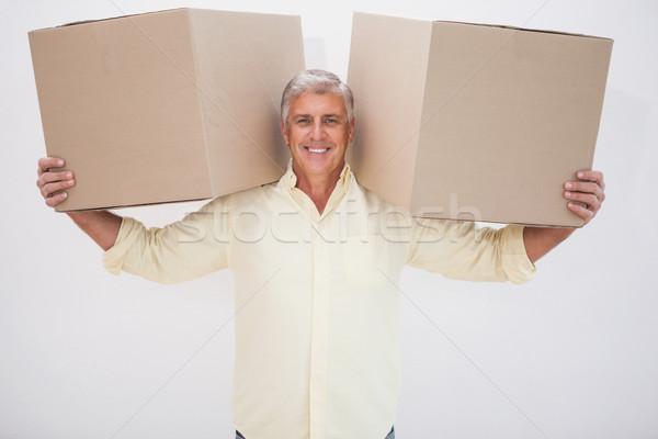 Uśmiechnięty człowiek równoważenie ciężki tektury pola Zdjęcia stock © wavebreak_media