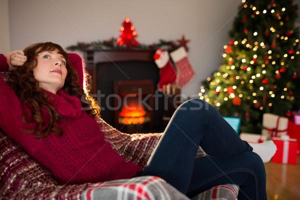 Pretty redhead sitting on armchair thinking  Stock photo © wavebreak_media
