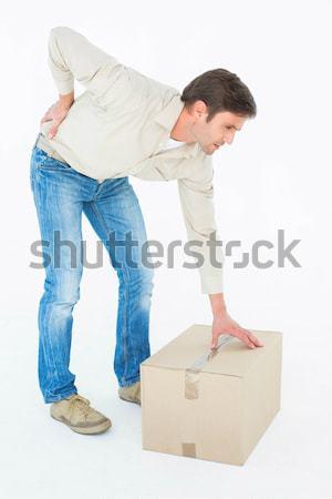 Courier man picking up cardboard box Stock photo © wavebreak_media