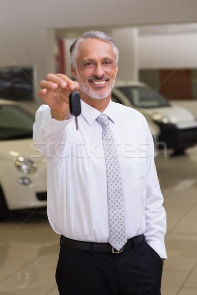 Venditore piedi offrendo chiavi della macchina showroom Foto d'archivio © wavebreak_media