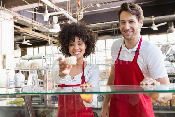 Souriant serveuse rouge tablier offrant Photo stock © wavebreak_media