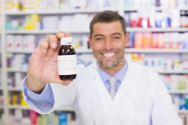 Jóképű gyógyszerész mutat gyógyszeres üveg kórház gyógyszertár Stock fotó © wavebreak_media
