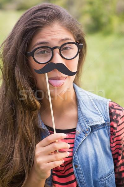 Joli brunette faux moustache herbe Photo stock © wavebreak_media