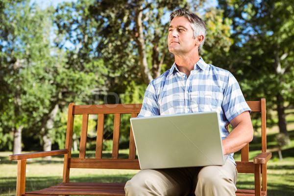 Homme séance parc banc utilisant un ordinateur portable Photo stock © wavebreak_media