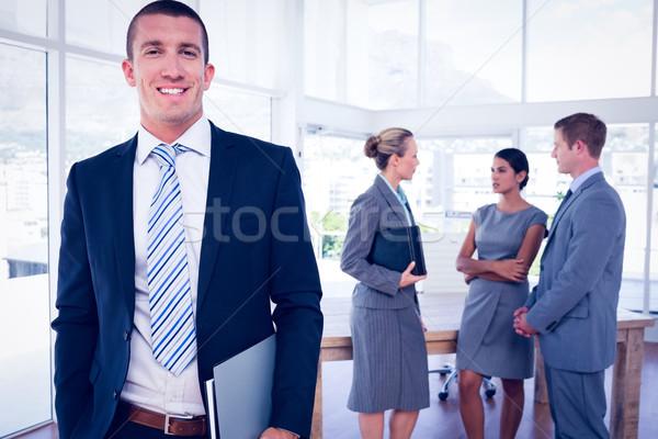 Zakenman glimlachend camera collega's achter man Stockfoto © wavebreak_media