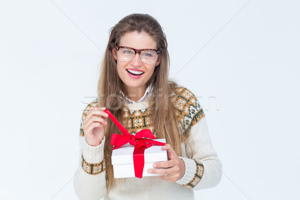 Happy geeky hipster smiling at camera and holding present Stock photo © wavebreak_media