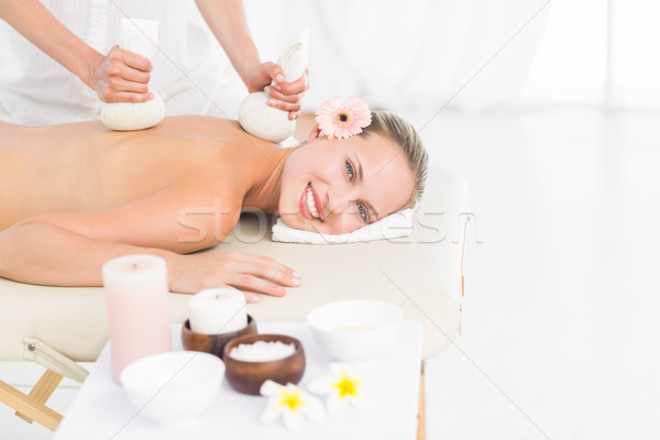 Beautiful blonde enjoying a herbal compress massage Stock photo © wavebreak_media