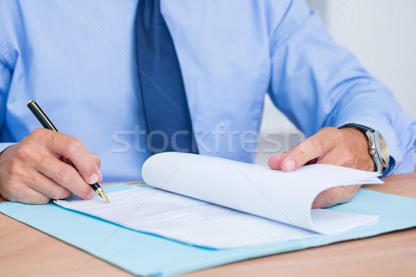 Glimlachend zakenman lezing ondertekening man pen Stockfoto © wavebreak_media