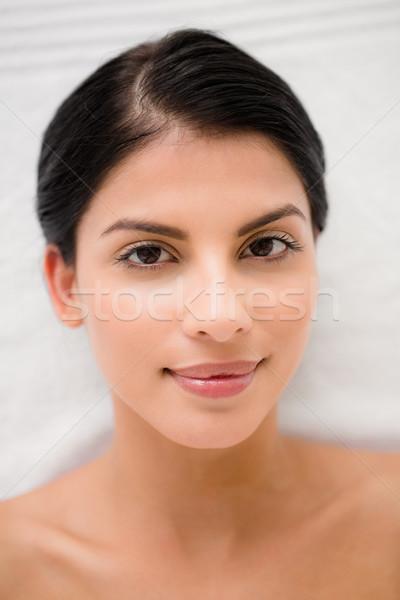 Pretty brunette enjoying a massage smiling at camera Stock photo © wavebreak_media